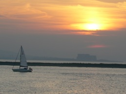 Peaceful sunset over Somerset with sailing boat and Hinckley point Nuclear power Station fading into the misty distance