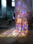 Stained glass window reflection on column at Gloucester cathedral