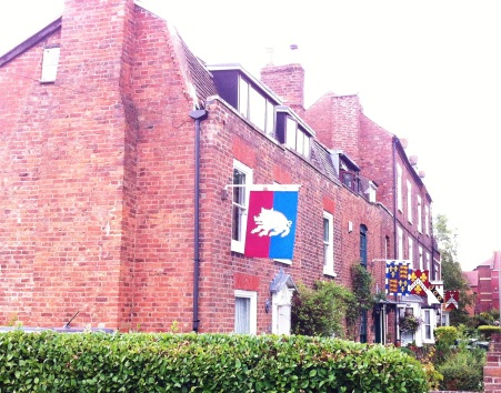 cottages opposite Tewkesbury Abbey showing banners
