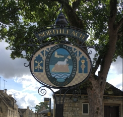 Northleach town sign showing it was granted an Annual Market Town Charter in 1227