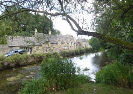Cottages in Bibury opposite Rack Isle. It gets its name from the wooden racks that were used to stretch the cloth made at Arlington Mill. It is surrounded by the River Colne and Arlington Mill stream.