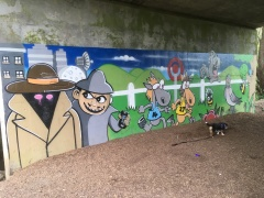 Graffiti or art lines the tunnel in the park